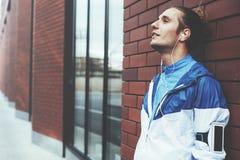 Portrait de coureur se tenant sur la rue près du mur de briques et du repos, le brassard avec le téléphone portable et les écoute photos libres de droits