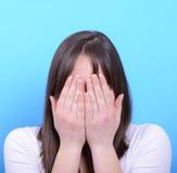 Portrait de couvrir son visage de mains sur le fond bleu Image libre de droits
