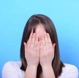Portrait de couvrir son visage de mains sur le fond bleu Images stock