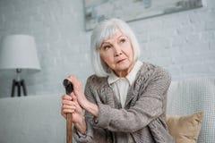 portrait de dame grise songeuse de cheveux avec le bâton de marche en bois regardant loin tout en se reposant sur le sofa image stock