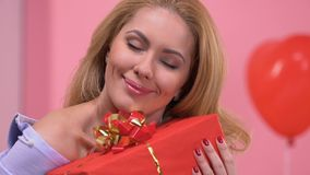 Portrait de dame heureuse étreignant le cadeau de son ami affectueux le jour de valentines banque de vidéos