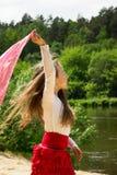 portrait de danse cutly mignonne de fille avec l'écharpe rouge à la rivière Photographie stock libre de droits