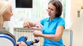 Portrait de dentiste féminin parlant à son patient au sujet d'hygiène de dents photographie stock libre de droits