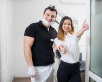 Portrait de dentiste masculin amical avec le patient féminin heureux après traitement dans le bureau dentaire moderne dentistry photo stock