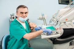 Portrait de dentiste masculin supérieur avec l'équipement dentaire dans le bureau dentaire photo stock