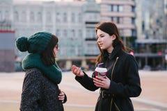 Portrait de deux élégants et belles amies se tenant sur la rue et le milieu parlant de la ville Photos stock