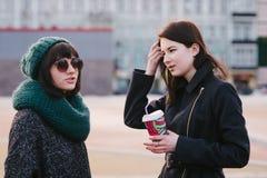 Portrait de deux élégants et de belles amies se tenant sur le milieu de la rue de ville Photos stock