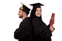 Portrait de deux étudiants musulmans arabes de graduation heureux D'isolement au-dessus du fond blanc Photographie stock libre de droits