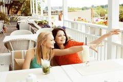 Portrait de deux amie assez modernes dans l'inte d'air ouvert de café Image libre de droits