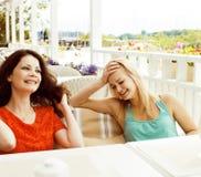 Portrait de deux amie assez modernes dans l'inte d'air ouvert de café Photo stock