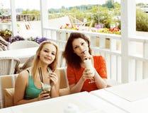 Portrait de deux amie assez modernes dans l'inte d'air ouvert de café Photographie stock libre de droits