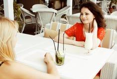 Portrait de deux amie assez modernes dans l'inte d'air ouvert de café Photo libre de droits