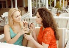 Portrait de deux amie assez modernes le boire intérieur d'air ouvert de café et en parlant, ayant la causerie et le coctail Photo libre de droits