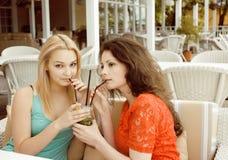 Portrait de deux amie assez modernes le boire intérieur d'air ouvert de café et en parlant, ayant la causerie et le coctail Photos stock