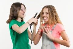 Portrait de deux amies adolescentes faisant la coiffure à la maison Image stock