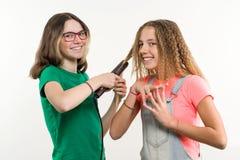 Portrait de deux amies adolescentes faisant la coiffure à la maison Fond blanc Image libre de droits