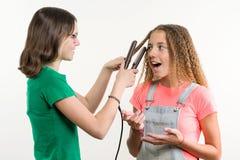 Portrait de deux amies adolescentes faisant la coiffure à la maison Fond blanc Photographie stock