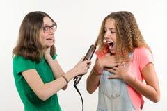 Portrait de deux amies adolescentes faisant la coiffure à la maison Fond blanc Photos libres de droits