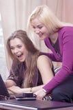 Portrait de deux amies caucasiennes émotives avec l'ordinateur portable ayant l'amusement Images stock