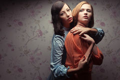Portrait de deux amies magnifiques dans des robes bleues et d'orange Photographie stock