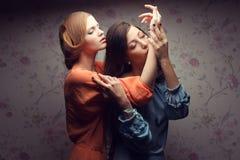 Portrait de deux amies magnifiques dans des robes bleues et d'orange Photos stock