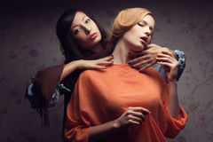 Portrait de deux amies magnifiques dans des robes bleues et d'orange Image libre de droits