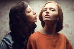 Portrait de deux amies magnifiques dans des robes bleues et d'orange Images libres de droits