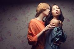 Portrait de deux amies magnifiques dans des robes bleues et d'orange Photo stock
