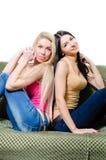 Portrait de deux amies ou soeurs assez jeunes sur le sofa Photos libres de droits