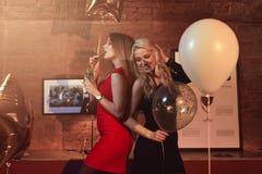 Portrait de deux amies sexy ayant le cocktail potable d'amusement dans le restaurant moderne décoré des ballons Photographie stock libre de droits