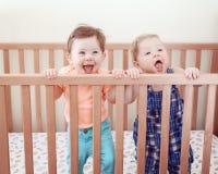 Portrait de deux amis drôles adorables mignons d'enfants de mêmes parents de bébés de neuf mois se tenant dans rire de sourire de Images stock