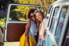 Portrait de deux amis féminins se tenant près de campervan Image stock
