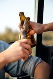 Portrait de deux amis grillant avec des bouteilles de bière dans la voiture Images libres de droits