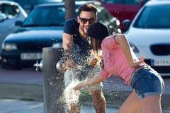 Portrait de deux amis jouant avec une fontaine dans la rue Photographie stock