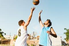 Portrait de deux amis jouant le basket-ball sur la cour Photo libre de droits