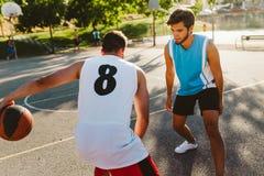 Portrait de deux amis jouant le basket-ball sur la cour Photographie stock