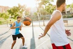 Portrait de deux amis jouant le basket-ball sur la cour Images stock