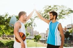 Portrait de deux amis jouant le basket-ball sur la cour Image stock