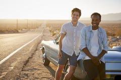Portrait de deux amis masculins appréciant le voyage par la route se tenant à côté de la voiture classique sur la route de désert photo stock