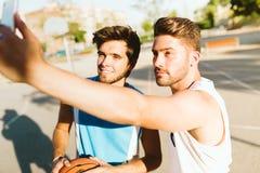 Portrait de deux amis prenant un selfie sur la cour Images stock