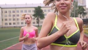 Portrait de deux athlètes courant par le stade Un dans des écouteurs écoute la musique clips vidéos