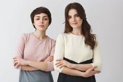 Portrait de deux beaux amis féminins d'université avec les cheveux foncés, posant pour l'album photos d'obtention du diplôme dans Image stock
