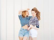 Portrait de deux belles amies à la mode dans les shorts de denim et le T-shirt rayé posant le nex au mur de verre Fille montrant  Photo libre de droits