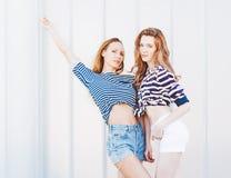 Portrait de deux belles amies à la mode dans les shorts de denim et le T-shirt rayé posant le nex au mur de verre outdoors Guerre Photographie stock