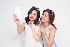 Portrait de deux belles femmes à la mode asiatiques prenant le selfie Photographie stock libre de droits