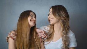 Portrait de deux belles filles souriant et regardant l'appareil-photo dans le studio banque de vidéos