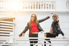 Portrait de deux belles jeunes amies avec les tasses de café de papier dans des mains Photographie stock
