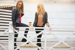 Portrait de deux belles jeunes amies avec les tasses de café de papier dans des mains Photos libres de droits