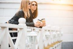 Portrait de deux belles jeunes amies avec les tasses de café de papier dans des mains Images libres de droits