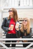 Portrait de deux belles jeunes amies avec les tasses de café de papier dans des mains Image stock